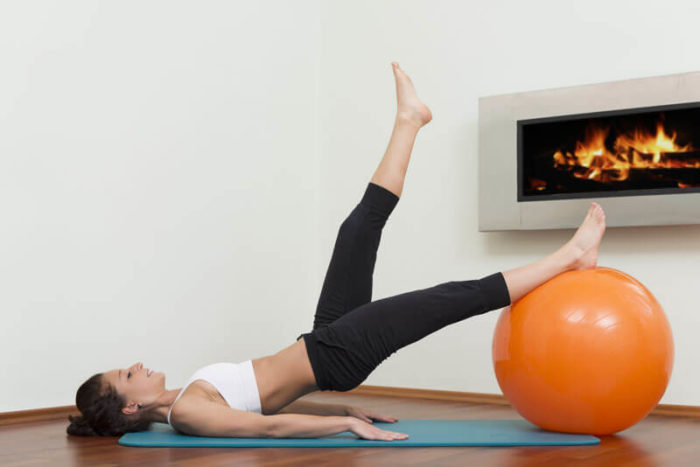 Woman performing stability ball exercise